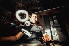Vaper with beard produce many steam rings. Men with beard vape and produse steam rings stock photo