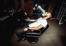 Vaper with beard produce many steam rings. Men with beard vape and produse steam rings stock images