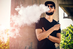 Vaper with beard in sunglasses vaping outdoor. Men with beard vaping outdoor in sunglasses Stock Photo