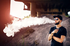 Vaper with beard in sunglasses vaping outdoor Royalty Free Stock Photo