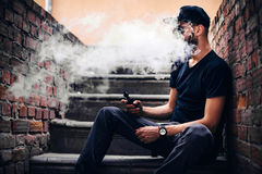 Vaper with beard in sunglasses vaping outdoor. Men with beard vaping outdoor in sunglasses royalty free stock photography