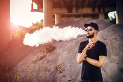 Vaper with beard in sunglasses vaping outdoor. Men with beard vaping outdoor in sunglasses royalty free stock images