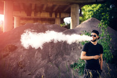 Vaper with beard in sunglasses vaping outdoor. Men with beard vaping outdoor in sunglasses royalty free stock photo
