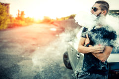 Vaper with beard in sunglasses vaping outdoor stock photography