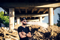 Vaper with beard in sunglasses vaping outdoor. Men with beard vaping outdoor in sunglasses stock photography