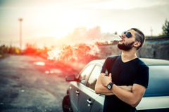 Vaper with beard in sunglasses vaping outdoor. Men with beard vaping outdoor in sunglasses Royalty Free Stock Image