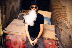 Vaper with beard in sunglasses vaping outdoor Royalty Free Stock Images