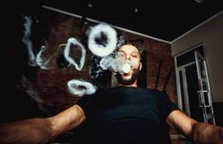 Vaper mit Barterzeugnis viele dämpfen Ringe stockfotografie