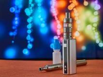 Vaping与坦克雾化器和瓶的mod e香烟在五颜六色的背景 免版税库存图片