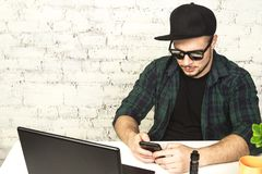 vaping年轻的人坐在有一杯咖啡的办公室和 库存图片