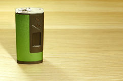 vaping的电子香烟一个绿色boxmod设备在木表面关闭  库存照片