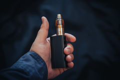 Vaping设备在人` s手上 电子香烟, vape 免版税图库摄影