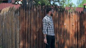 Vaping Bearded Man. Young bearded hipster man in sunglasses and a checkered shirt smokes an electronic cigarette near a wooden palisade in slow motion stock video footage