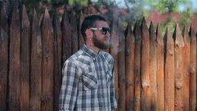 Vaping Bearded Man. Man. young bearded hipster man in sunglasses and a checkered shirt smokes an electronic cigarette near a wooden palisade in slow motion stock footage