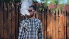 Vaping Bearded Man. Man. young bearded hipster man in sunglasses and a checkered shirt smokes an electronic cigarette near a wooden palisade in slow motion stock video footage