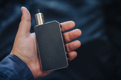 Vaping device in in the man`s hand. Electronic cigarette, vape. Stock Photos