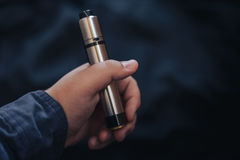 Vaping device in in the man`s hand. Electronic cigarette, vape Stock Image
