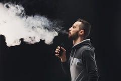 Vaping Ezigarette des jungen Mannes mit Rauche auf Schwarzem Lizenzfreie Stockfotografie