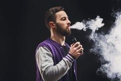 Vaping Ezigarette des jungen Mannes mit Rauche auf Schwarzem Stockfotografie