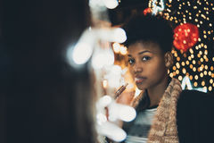 Vaping girl on night city street. Portrait of young cute curly afro american girl surrounded by night city New Year or Christmas lights, garlands and decoration royalty free stock photos