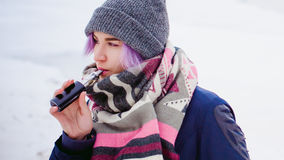 Vaping girl. Winter street portrait of a woman hipster, purple-dyed hair, a gray knitted hat and scarf. woman smokes an electronic cigarette in the street near royalty free stock photo