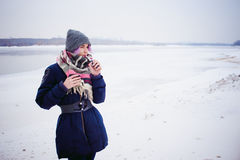 Vaping girl. Winter street portrait of a woman hipster, purple-dyed hair, a gray knitted hat and scarf. woman smokes an electronic cigarette in the street near stock image