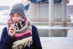 Vaping girl. Winter street portrait of a woman hipster, purple-dyed hair, a gray knitted hat and scarf. woman smokes an electronic cigarette in the street near stock photos