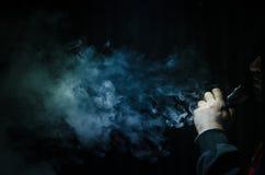 Vaping mężczyzna trzyma mod Chmura opary Czarny tło Vaping elektroniczny papieros z mnóstwo dymem Zdjęcia Stock