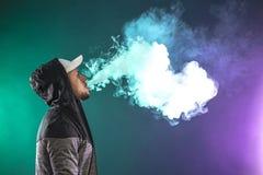 Vaping man and a cloud of vapor. Vaping man. A cloud of vapor. dark blue background stock images