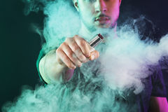 Vaping man holding a mod. A cloud of vapor. Black background Stock Photo
