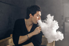 Vaping man holding a mod. A cloud of vapor. Black background. Smoking electronic cigarette Vape advertisement concept stock images