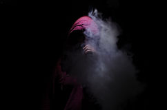 Vaping man holding a mod. A cloud of vapor. Black background. Vaping an electronic cigarette with a lot of smoke. Vape concept Royalty Free Stock Photo