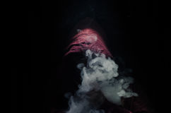 Vaping man holding a mod. A cloud of vapor. Black background. Vaping an electronic cigarette with a lot of smoke. Vape concept Stock Image