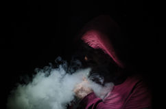 Vaping man holding a mod. A cloud of vapor. Black background. Vaping an electronic cigarette with a lot of smoke. Vape concept stock photo