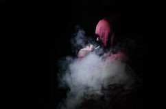 Vaping man holding a mod. A cloud of vapor. Black background. Vaping an electronic cigarette with a lot of smoke. Vape concept Stock Photos