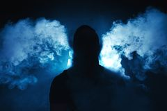 Vaping man holding a mod. A cloud of vapor. Dark blue background royalty free stock image