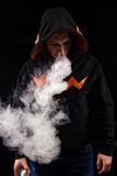 Vaping man in the hood holding a mod. A cloud of vapor. Black background Royalty Free Stock Image