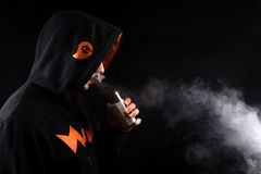 Vaping man in the hood holding a mod. A cloud of vapor. Black background Royalty Free Stock Images