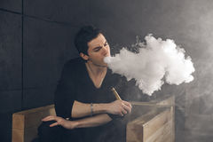 Vaping man som rymmer en ändring Ett moln av dunsten Svart bakgrund Arkivfoto