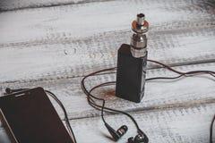 Vaping odparowalnik, przyrząd, cig gadżet vape i smartphone z hełmofonami lub, Obraz Royalty Free