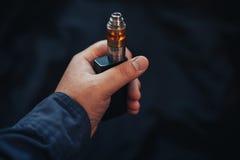 Vaping przyrząd wewnątrz w mężczyzna ` s ręce Elektroniczny papieros, vape Fotografia Stock