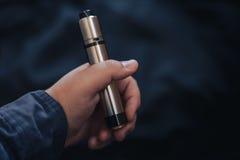 Vaping przyrząd wewnątrz w mężczyzna ` s ręce Elektroniczny papieros, vape Obraz Stock