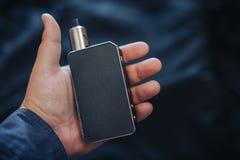 Vaping przyrząd wewnątrz w mężczyzna ` s ręce Elektroniczny papieros, vape Zdjęcia Stock