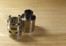 Vaping rebuildable dripping atomizer RDA on wooden surface with copy space close up.  Stock Image