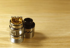 Vaping rebuildable dripping tank atomizer RDTA on wooden surface with copy space Stock Photos