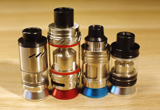 Vaping rebuildable dripping and tank atomizers RDTA, RTAon wooden surface close up Royalty Free Stock Images