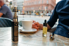 Vaping set on the table against the background of the city. Vaping set and cup of coffee on the table stock photos