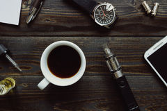 Vaping set, watch, coffee and smartphone on the wooden background. Hipster or bussinesman style. Vaping set, watch, smartphone and coffee on the dark table stock image