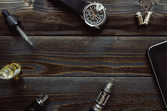 Vaping set, zegarek i pastylka na ciemnym stole, Modniś lub bussi Obraz Stock