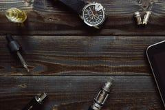 Vaping set, zegarek i pastylka na ciemnym stole, Modnisia lub bussinesman styl Obrazy Royalty Free